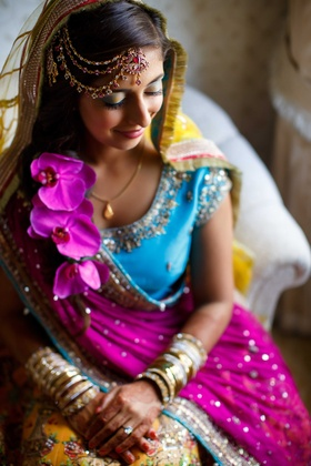 pakistani bride in purple blue and yellow traditional dress with headpiece sits and smiles