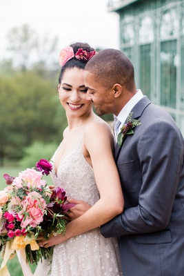 styled shoot wedding portrait inspiration, groom holding bride from behind while she looks back