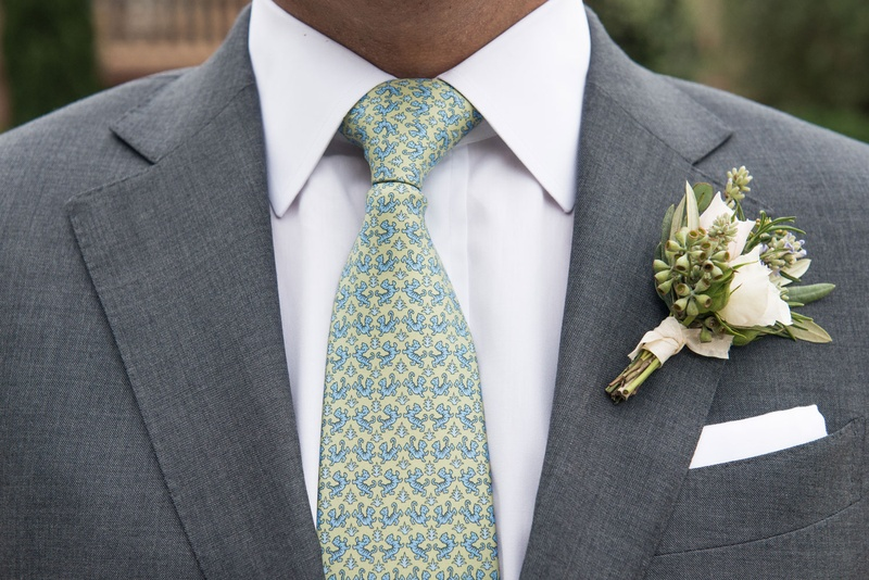 Groom with patterned tie yellow blue green with natural bouquet tied with ribbon greenery white rose