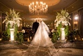 a father walks daughter bride down aisle white and green floral arrangements and chandelier