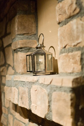 Oil lantern on exposed-stone wall mantle