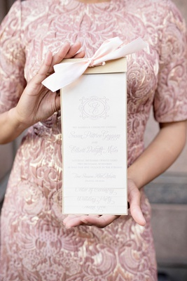 wedding guest in jacquard dress holding ceremony program monogram light print pink ribbon gold top