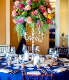 round navy tablescape vibrant florals tall arrangement silver candelabrum spanish flair wedding