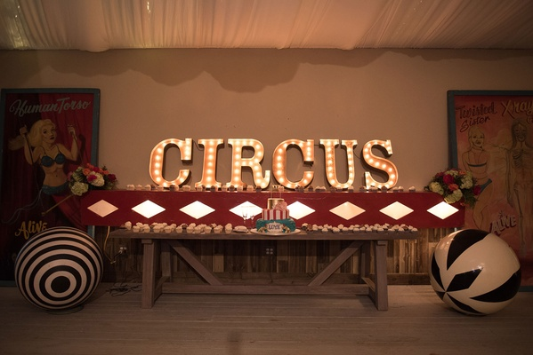 Dessert table with circus theme cake and cupcakes with circus marquee lettering and big balls