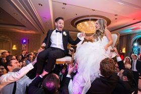 groom in lanvin, bride in reem acra during the horah at jewish wedding