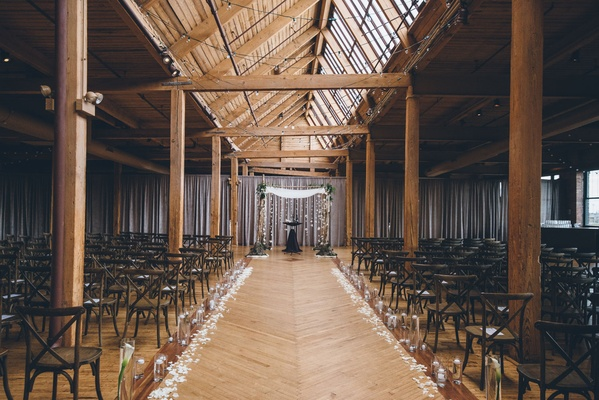 Wood beams rustic wedding ceremony venue with flowers and minimal decor birch branches