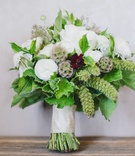 Bridal bouquet with white flowers, greenery, and scabiosa pods