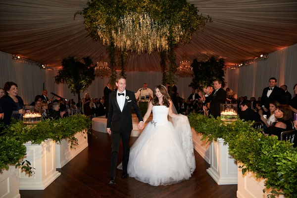 Bride in strapless vera wang wedding dress holding skirt and groom hand tuxedo wood floor chicago