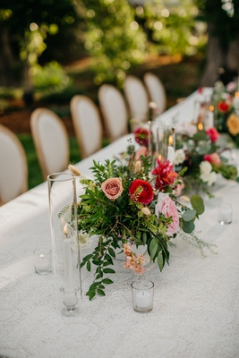 wedding reception long table taper candle pink red ranunculus greenery outdoor wedding reception
