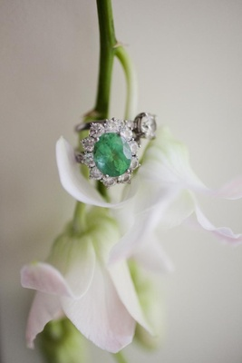 Oval emerald with halo of round diamonds on ring