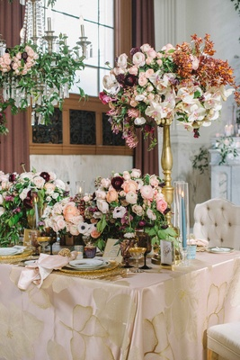 centerpiece with ranunculus and orchids on tall golden stand