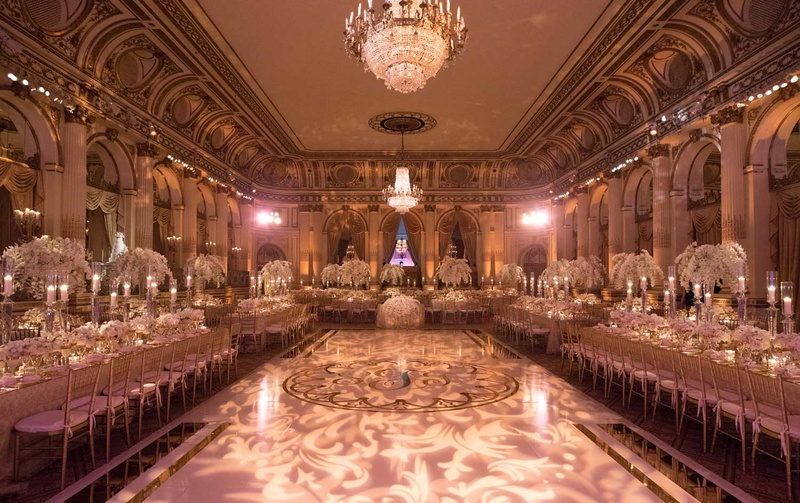 the plaza hotel wedding ballroom dance floor in center long tables chandeliers light projections