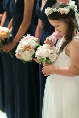 Flower girl in white sleeveless dress, small bouquet of white, peach roses, greenery, floral halo