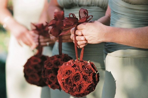 Bridesmaids holding spheres of red roses
