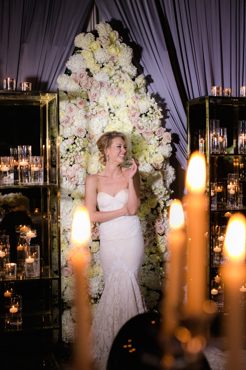 Bride in a fit-and-flare Inbal Dror dress in front of a panel of white hydrangeas, light yellow rose
