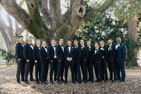 large group of groomsmen in tuxedos at black tie wedding, posed outdoors under tree