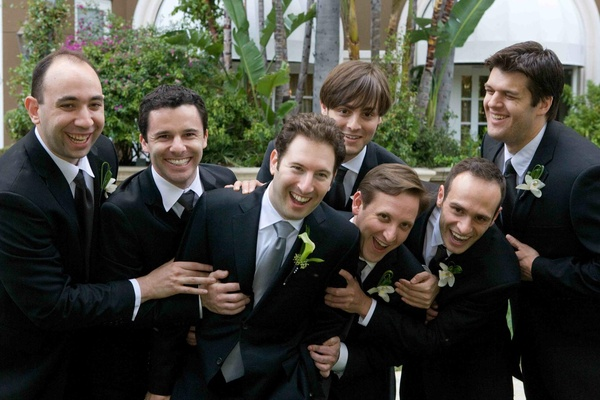 Groom with silver tie and groomsmen in black suits