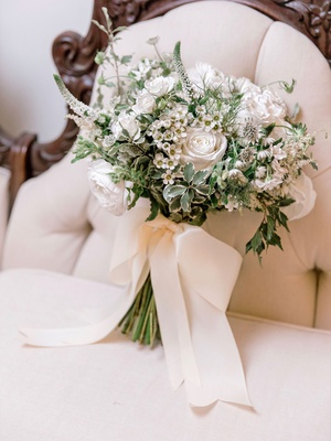 bridal bouquet soft greenery white flowers rose and additional blooms tied with white ribbon