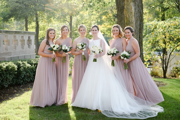wedding party bride in classic bateau neckline wedding dress bridesmaids in one shoulder dresses