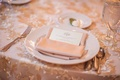 Wedding reception table with gold embroidered overlay, satin napkin and menu with couple's monogram
