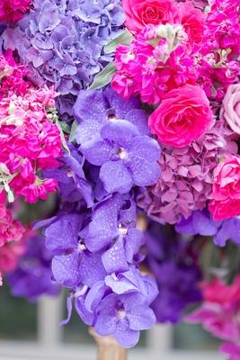 Wedding reception centerpiece of purple vanda orchids, hydrangeas, hot pink roses