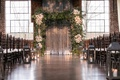 chuppah made with greenery and clumps of ivory flowers, interfaith ceremony