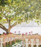 Grass aisle with swirled petals and garlands from trees