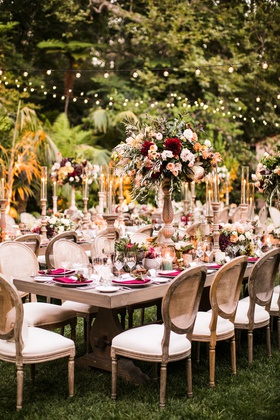 wedding reception outdoor rustic elegant fall color palette red greenery bistro lights cane chairs