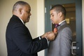 Father of groom puts on groom's boutonniere