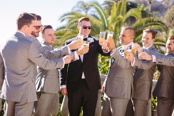 groom in Ermenegildo Zegna, groomsmen in Tommy Hilfiger toast to each other