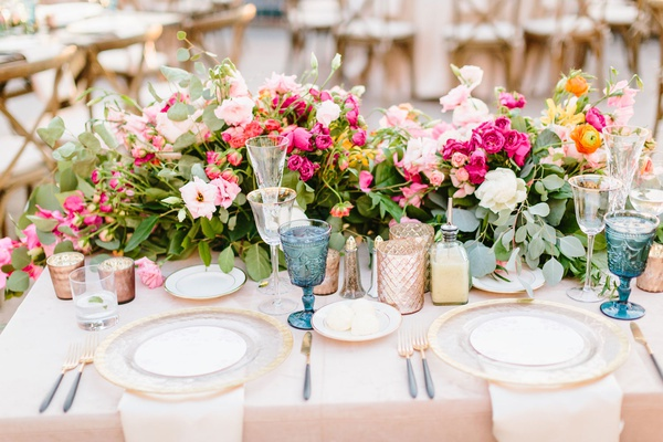 wedding reception sweetheart table gold charger plate pink and orange flowers greenery blue goblets