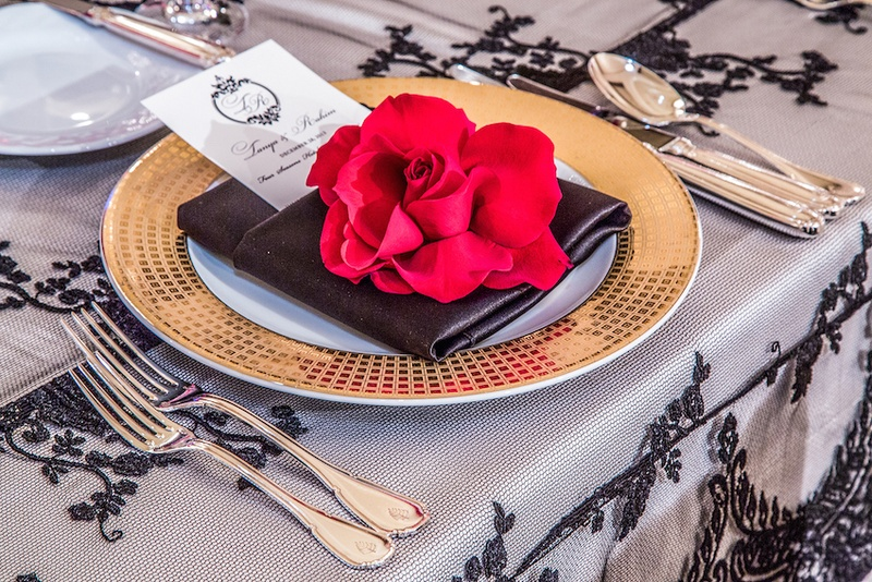 Elegant table setting with gold charger and flower decor