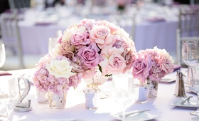Wedding reception table with lavender tablecloth, roses, and hydrangeas, sparkly table number