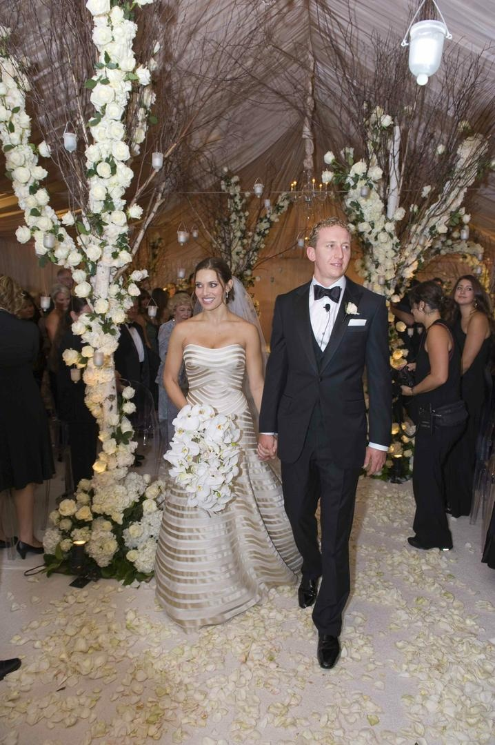Bride in a champagne Vera Wang gown and groom in a black tuxedo and bow tie