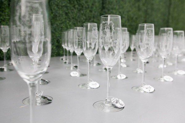 Custom champagne glasses with monogram and each guest's name etched in with mirror tags on stem