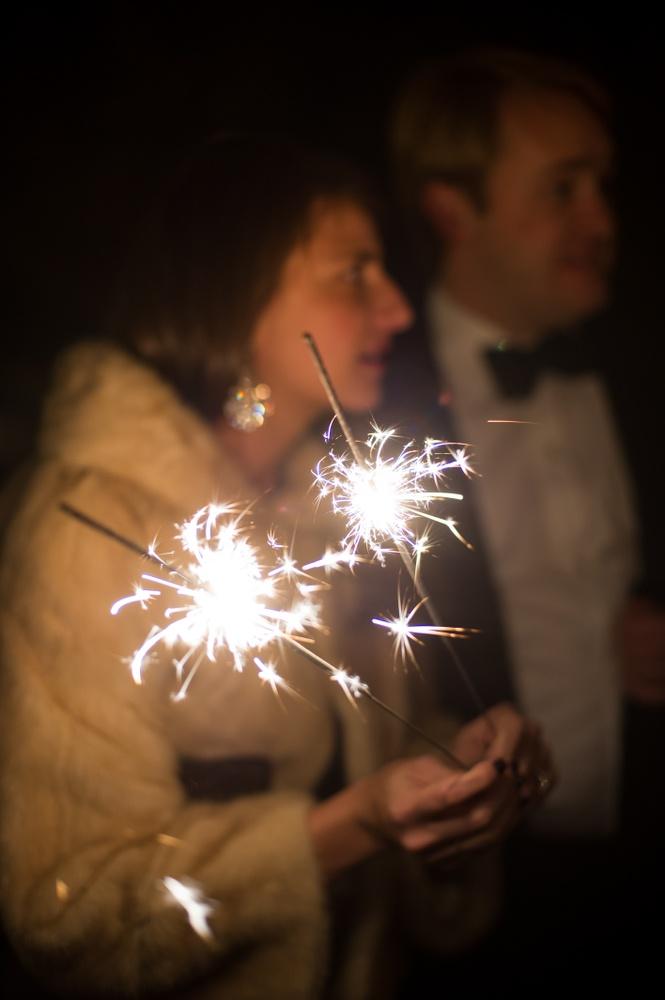 Wedding guest in fur jacket holds sparking sparklers