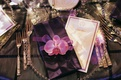 Silver bead charger plate with purple napkin and orchid