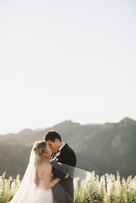 bride in strapless romona keveza wedding dress with sweetheart neckline kisses groom inhugo boss tux