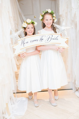 Flower girls in white dresses and flower crowns holding here comes the bride banner white ribbon