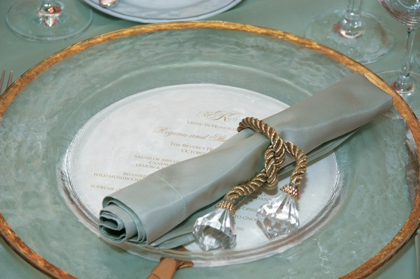 Place setting with clear gold-rimmed charger and celadon napkin for a wedding reception
