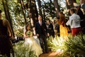 Bride and groom walk through forest aisle at ceremony