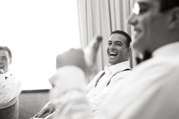 Black and white photo of groom laughing
