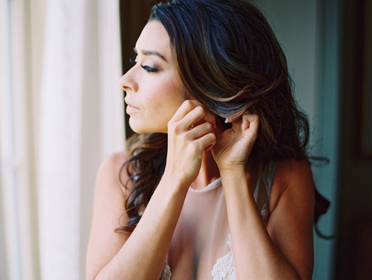 bride with soft curled brunette hair putting on earrings natural makeup soft lip dramatic eye