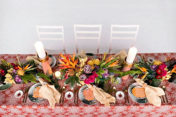 wedding reception orange linen palm print plates tropical centerpiece pink purple yellow flowers
