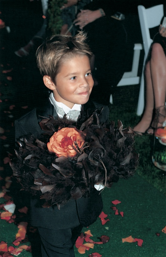 little boy ring bearer carries rings to the bride and groom on pillow