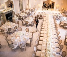 high angle view of ballroom reception with ivory flower centerpieces, tan chairs