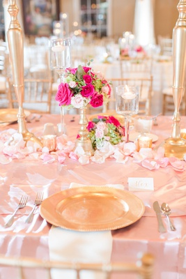 wedding reception table pink linen gold charger white napkin floating candles low pink rose flowers