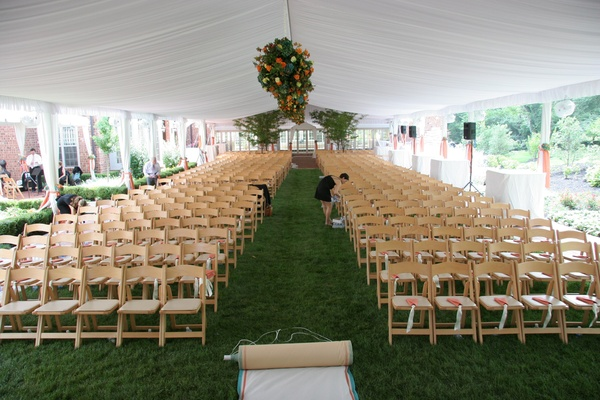 Tented wedding ceremony with floral arrangements suspended over the aisle