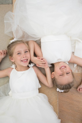 adorable flower girls in white dresses with tulle skirts lying down head to head while holding hands