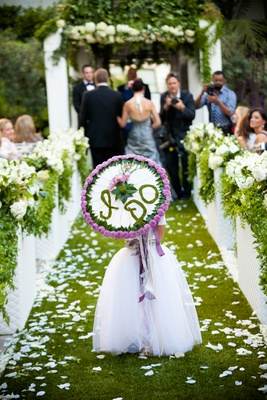 Flower girl walking down grass aisle holding umbrella